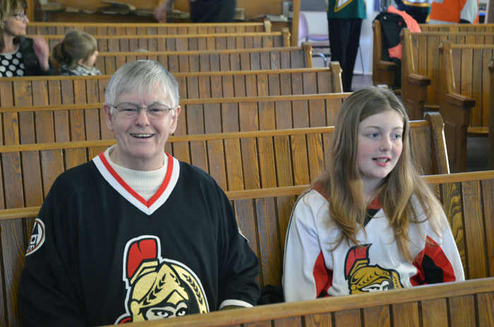 Two Ottawa Senators supporters. One favouring the home team and the other the away team jersey colours.